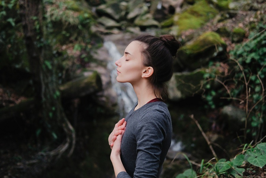 Young woman eyes closed, hands on chest, breathing outdoors in moss forest.