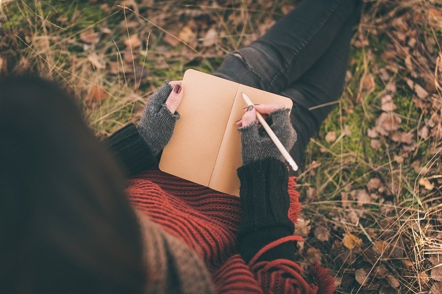 Woman writing in nature.