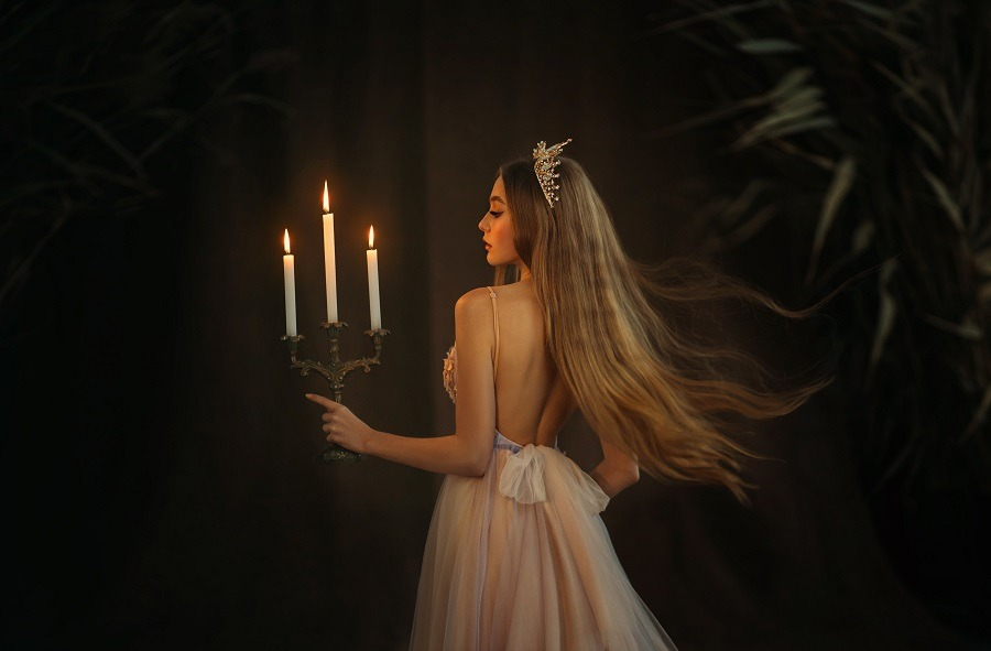 Beautiful medieval queen in white gown, holding a candlestick with burning candles in hand.