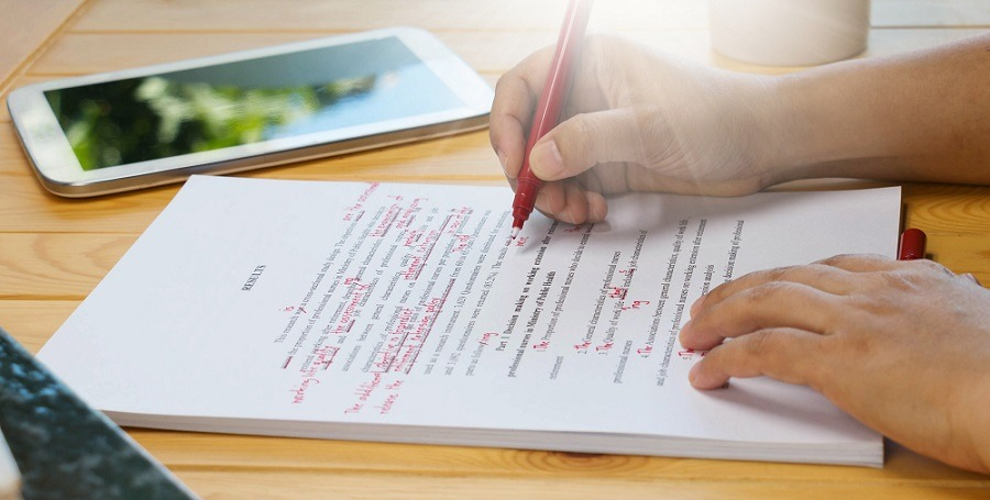 Hand holding red pen over proofreading text.