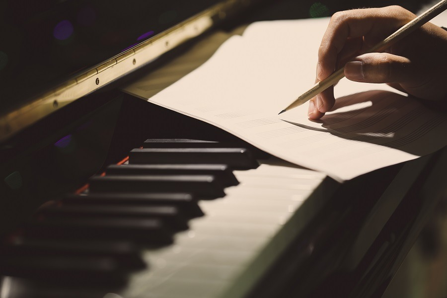 Composer writing music at the piano.