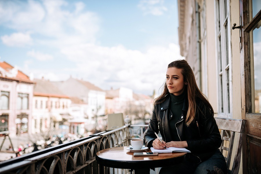 Lovely girl writing outdoors in the café with scenic view.