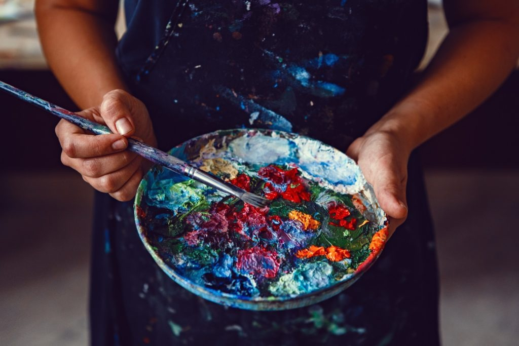 Hands of female artist holding messy palette with different color paints.