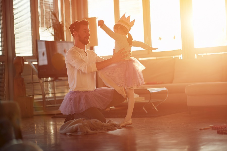 A little girl practices ballet at home with her dad.