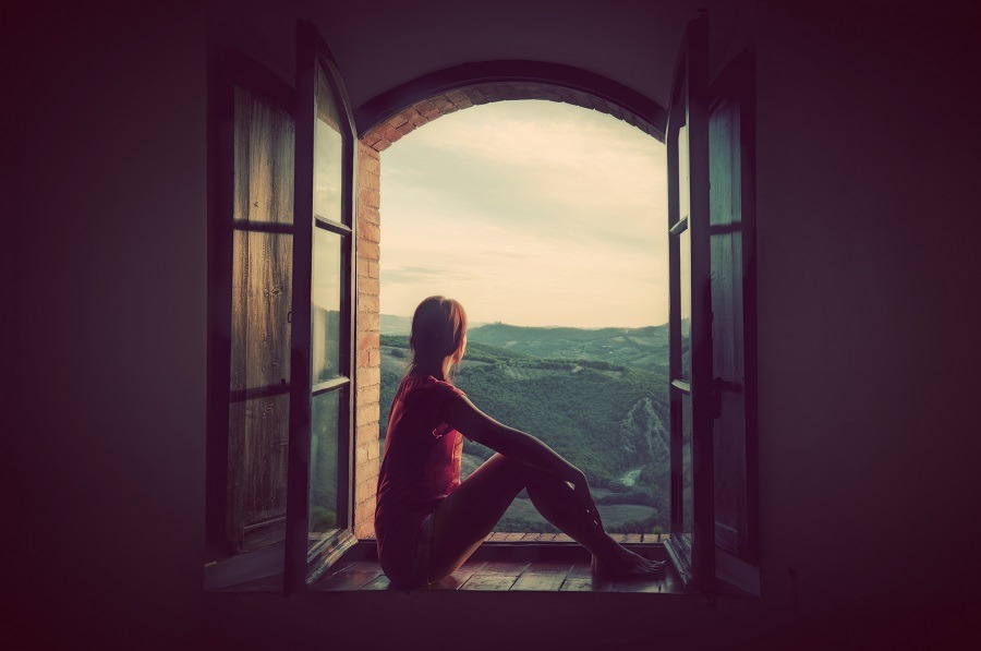 Lonely woman sitting in an open old window looking on the landscape of Tuscany, Italy.