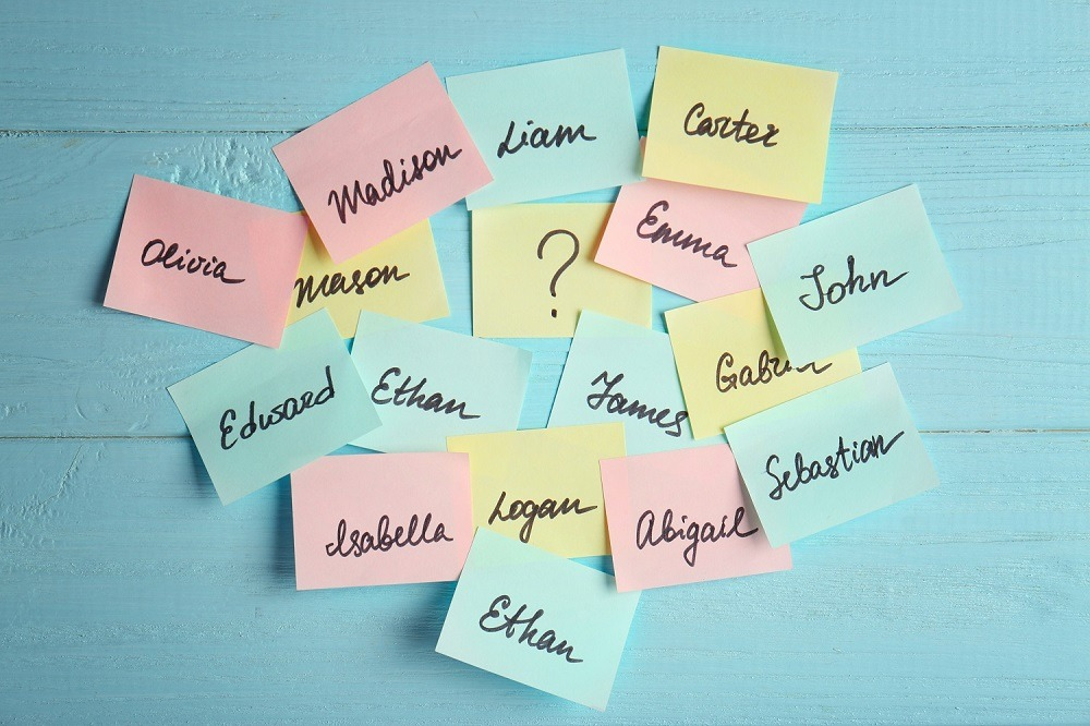 Paper stickers with different names on blue wooden background.