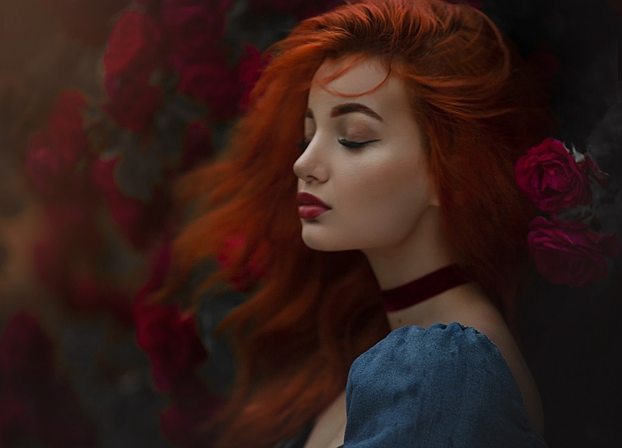 A pretty red haired girl in blue dress, hair blown by the wind.