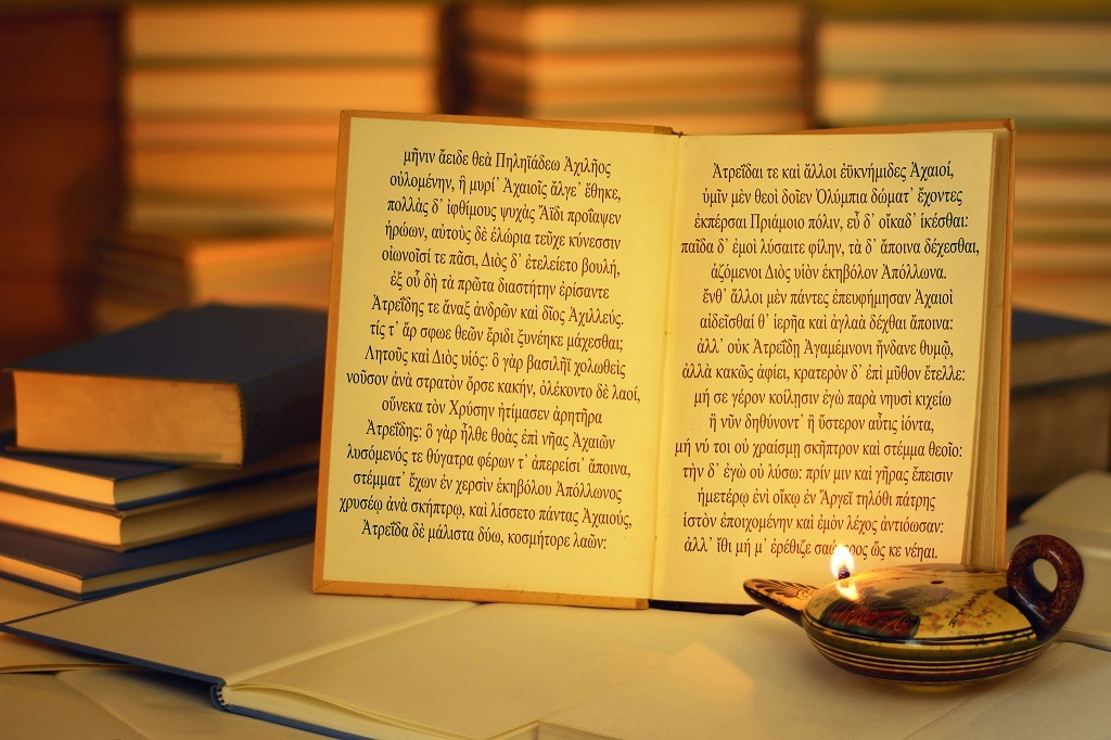 The opening lines of The Iliad written in the ancient Greek language illumined by oil lamp.