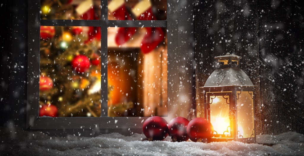 Christmas window sill and fireplace on snowy evening.