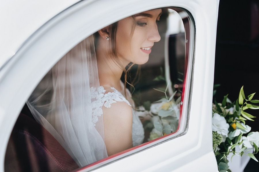 Beautiful bride with curly hair and a bouquet sits near the window in a white car.