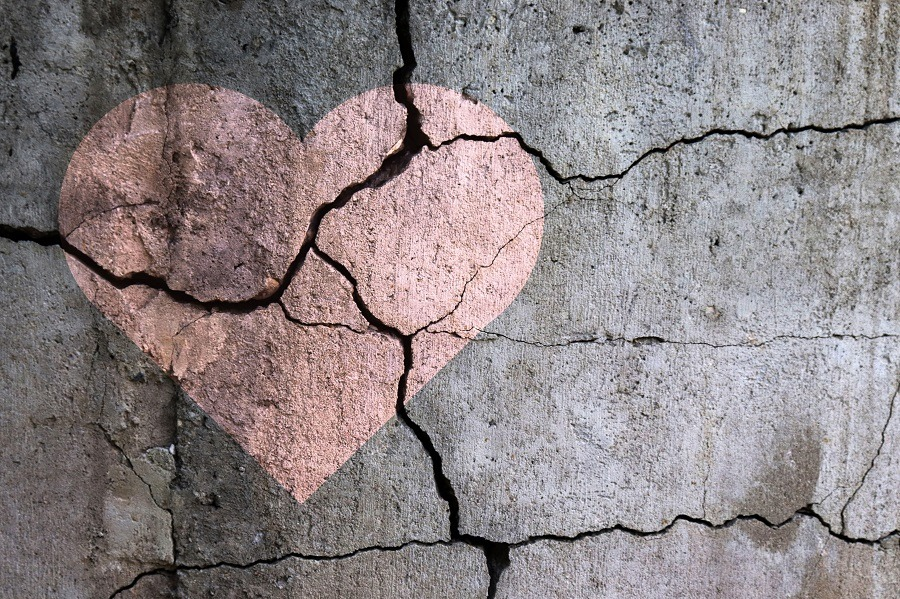 Drawing of a pink heart on a cracked wall.