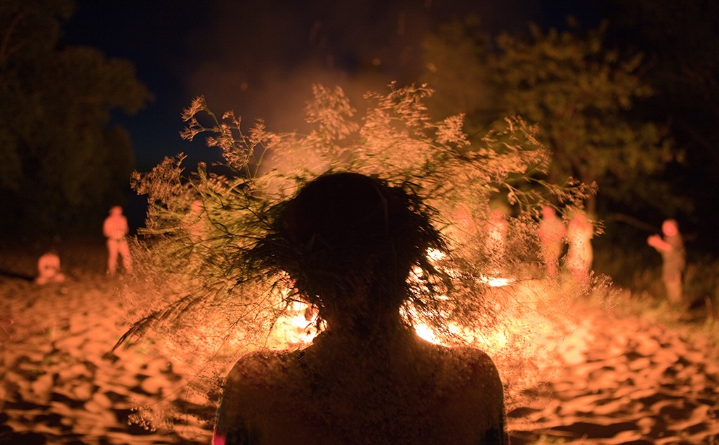 Silhouette of a woman wearing a flower crown by the fire