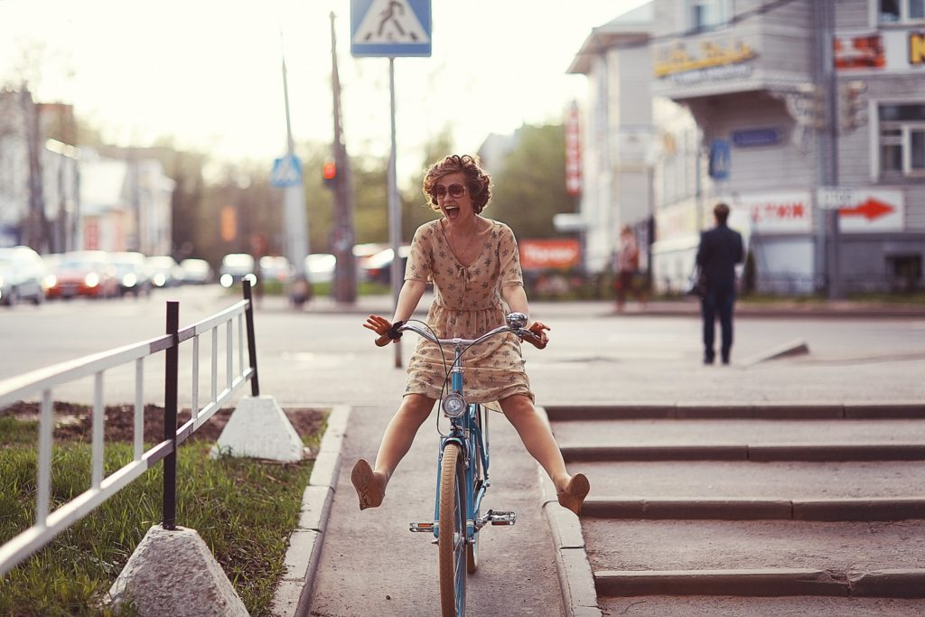 A lady in a summer dress playfully riding her bicycle.