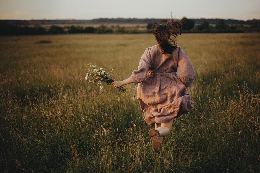 Beautiful woman in rustic dress running with wildflowers in hand in summer meadow in sunset.