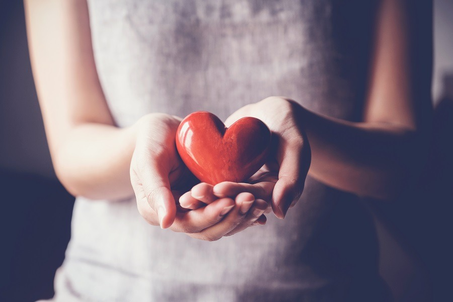 Close-up woman's cupped hands holding a red heart.