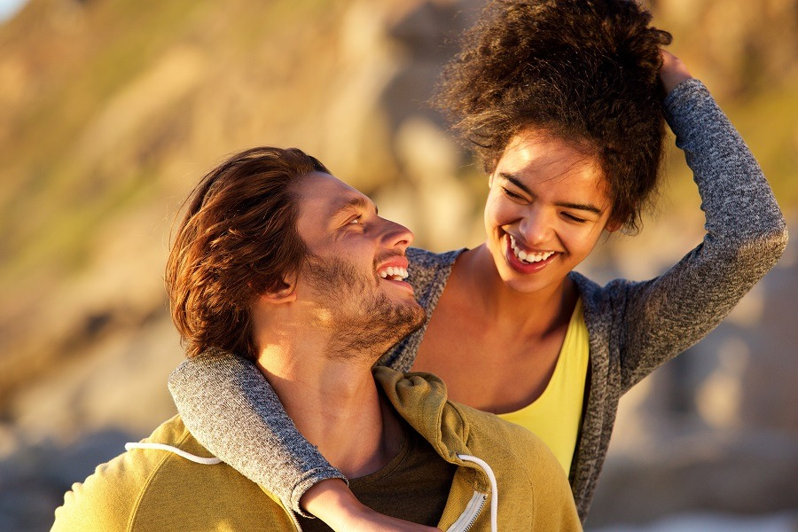 Attractive couple laughing together, man leaning on the woman.