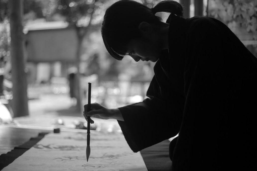 Silhouette of a Chinese girl doing calligraphy.