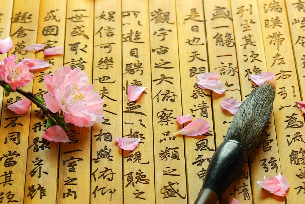 Pink flowers and brush on Chinese ancient bamboo slips.