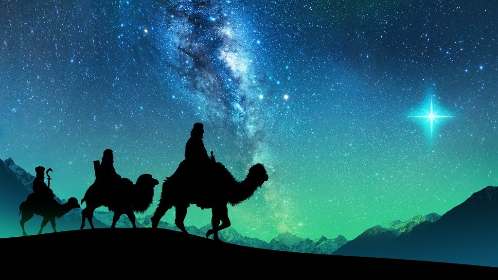 Silhouette of the three wise men riding a camel along the star path to meet the newborn Jesus.