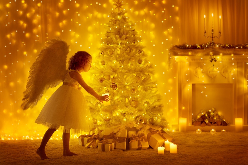 Golden Christmas and a girl angel lighting a candle.