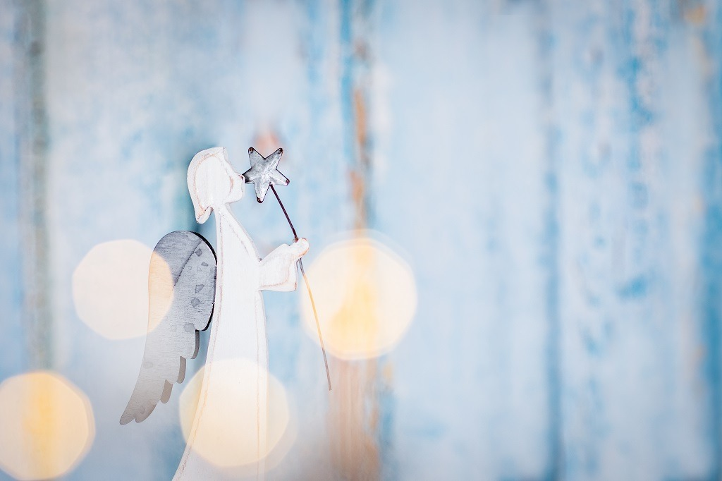 White angel Christmas decoration on blue background with lights.