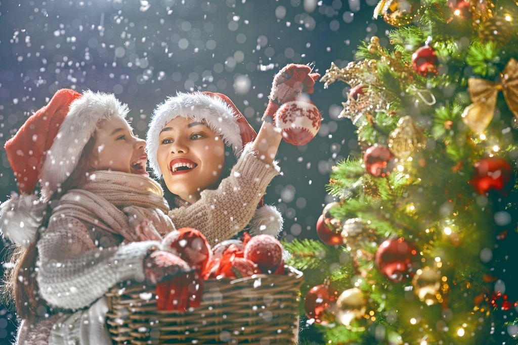 Mom and daughter decorate Christmas tree happily.