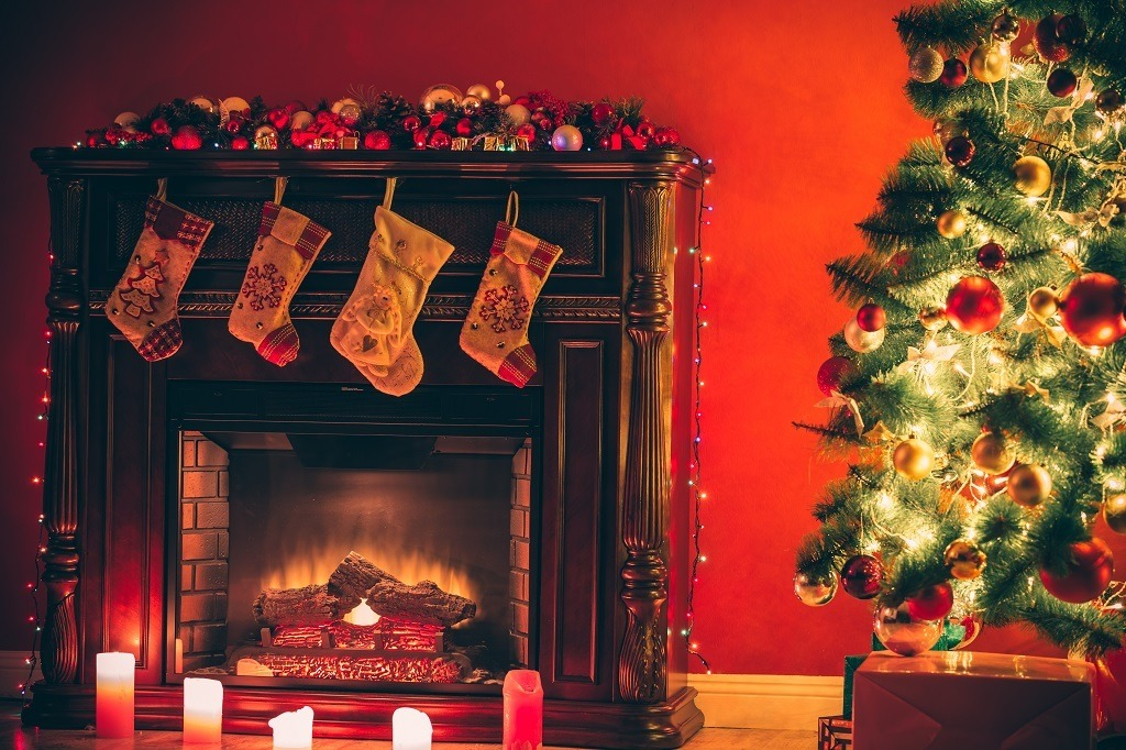 Beautiful room decorated with Christmas tree, gifts and fireplace with the glowing lights at night.
