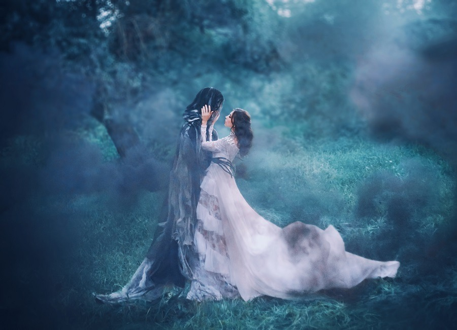Lady in white vintage lace dress hugs lover in foggy forest.