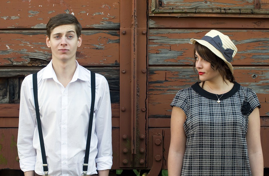 Retro young couple funny face standing side by side in backs to the wall.