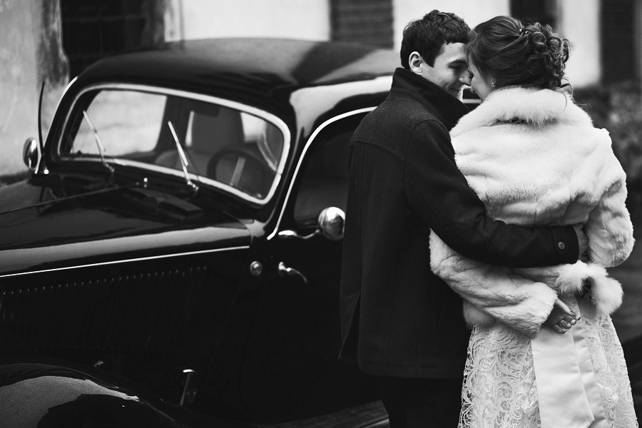 Elegantly dressed couple standing near a car faces close to each other, partly hugging.
