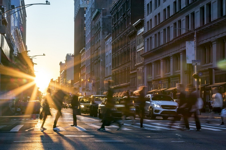 Rays of sunlight shine on the busy people walking across an intersection in Midtown Manhattan.