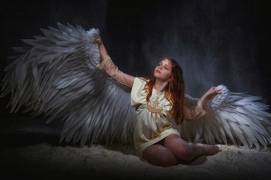 Beautiful white angel on a dark background with colored lighting.