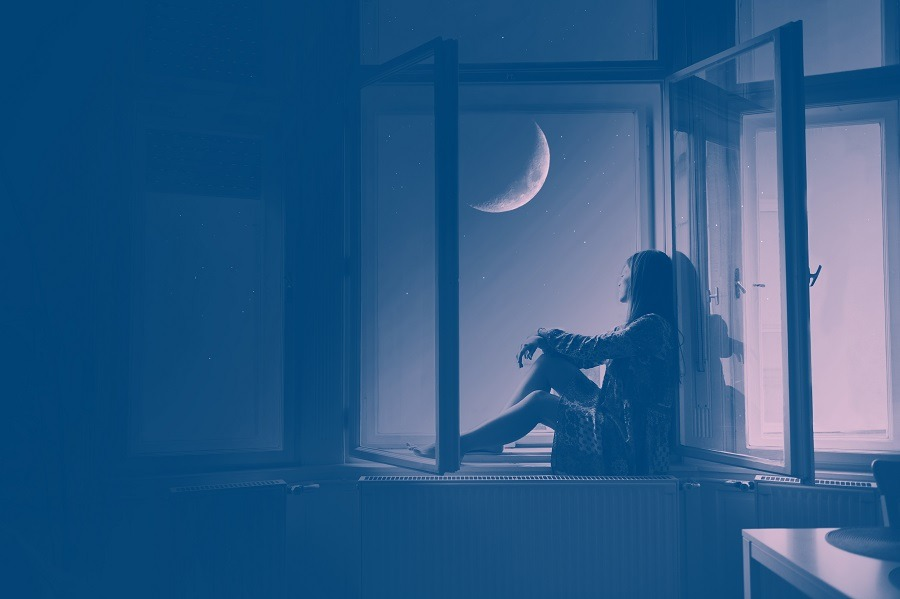 Woman alone in the room, sitting at the window looking the night sky.