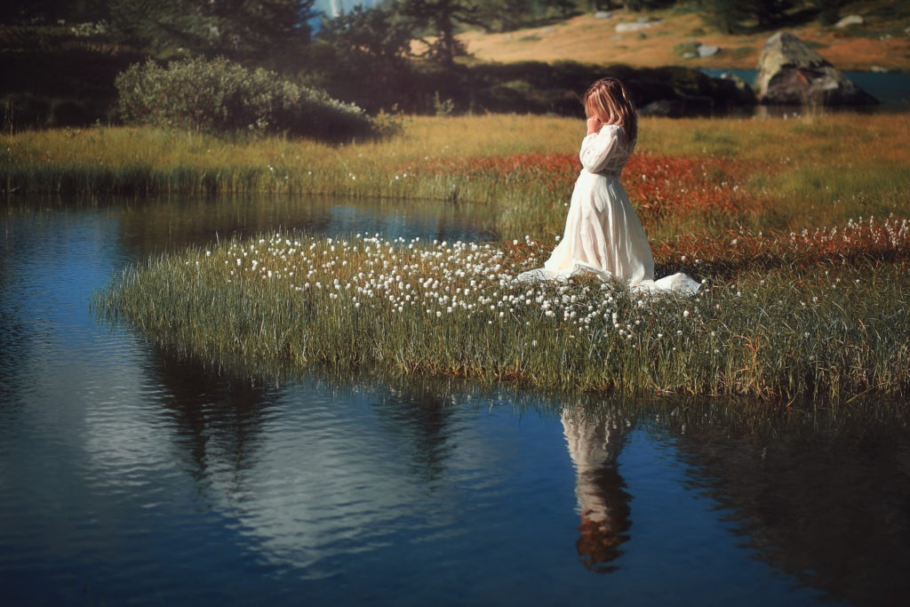 Woman with vintage dress in alpine lake kneeling and praying fervently.