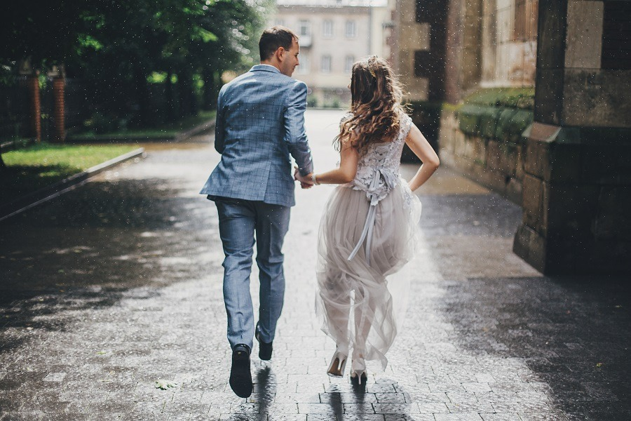 Stylish happy bride and groom running holding hands on background of old church in rainy street.
