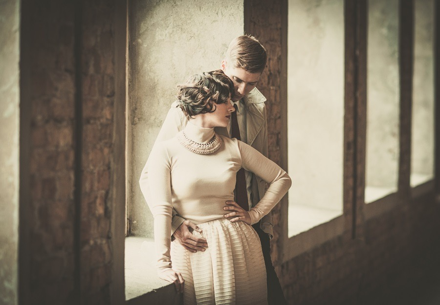 Beautiful vintage couple standing near window, woman leaning on to her man.