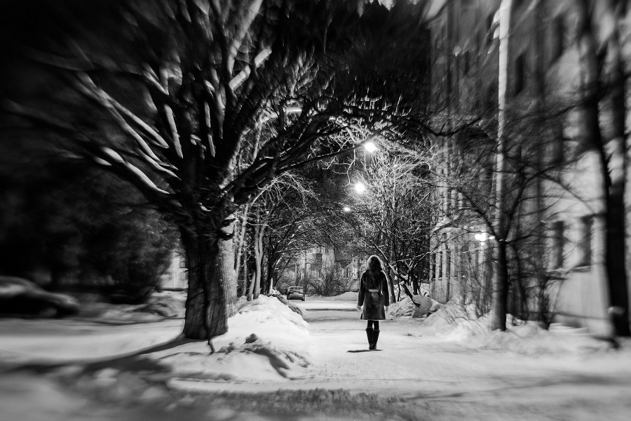 Lonely girl on the empty street in winter evening.