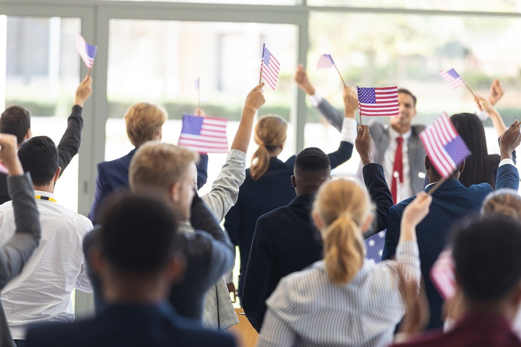 Politician having a speech and celebrating victory with people holding USA flaglets.