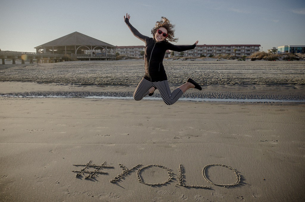 #YOLO hashtag written in the sand on the beach and an adult female jumping.