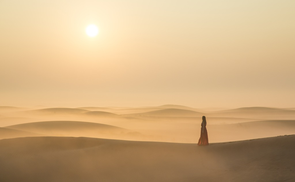 Woman in a desert at sunrise