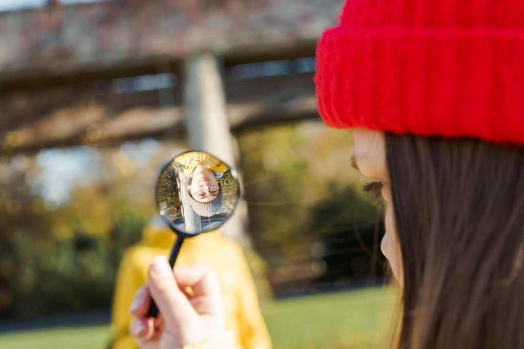 Girl in a red knitted hat looking through a magnifier on a boy.