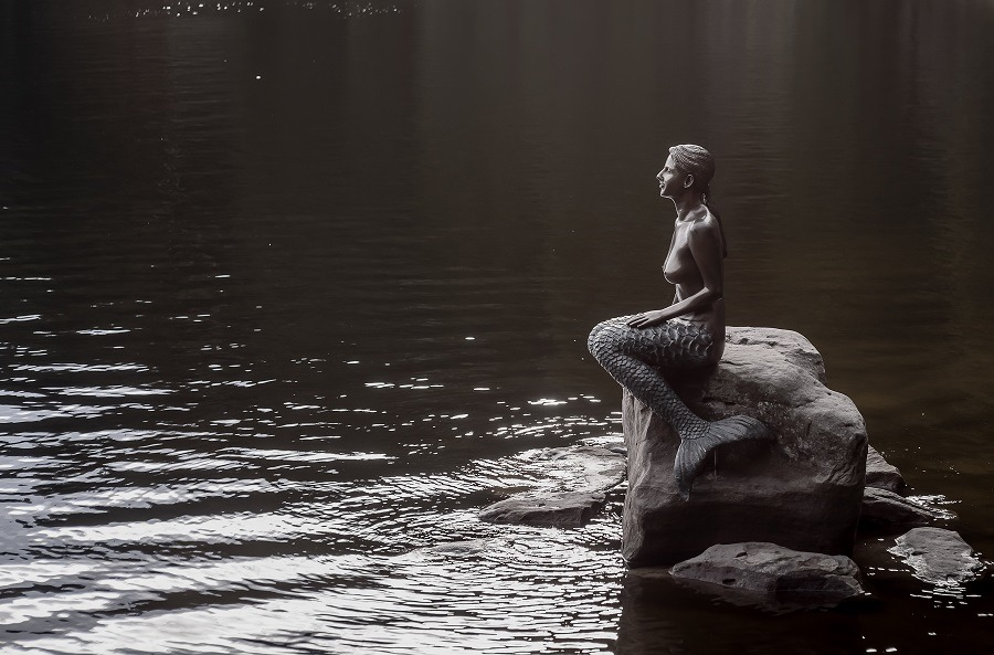 Statue of the little mermaid on a rock near a pond.