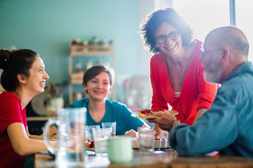 A family gathers around the kitchen table enjoying each other.