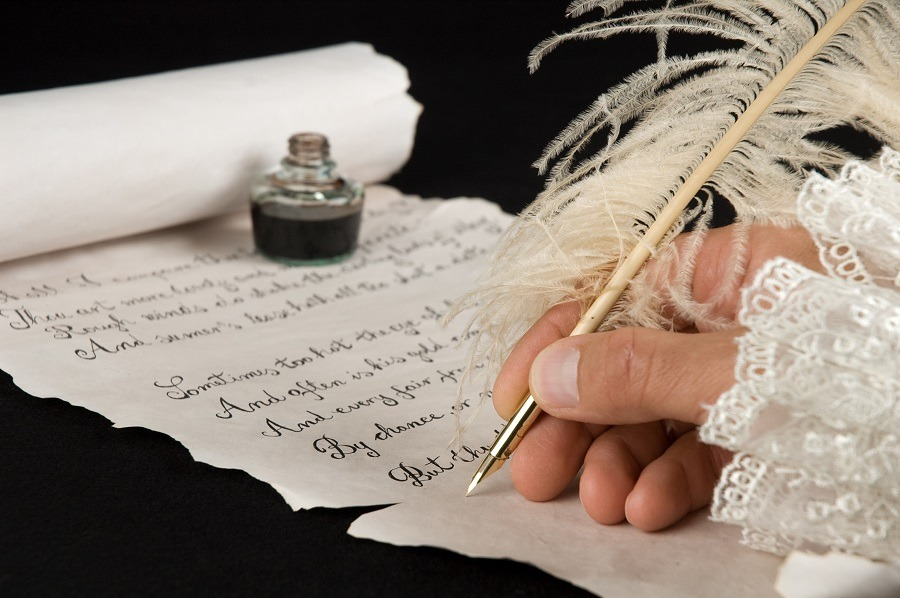 Close-up of a hand writing poetry with a quill pen.