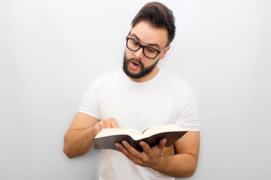 Young man reading aloud from book with emotions.