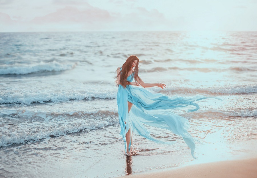 Young, slim woman with long legs dancing on the ocean, hair and train long blue dress fluttering in the wind.
