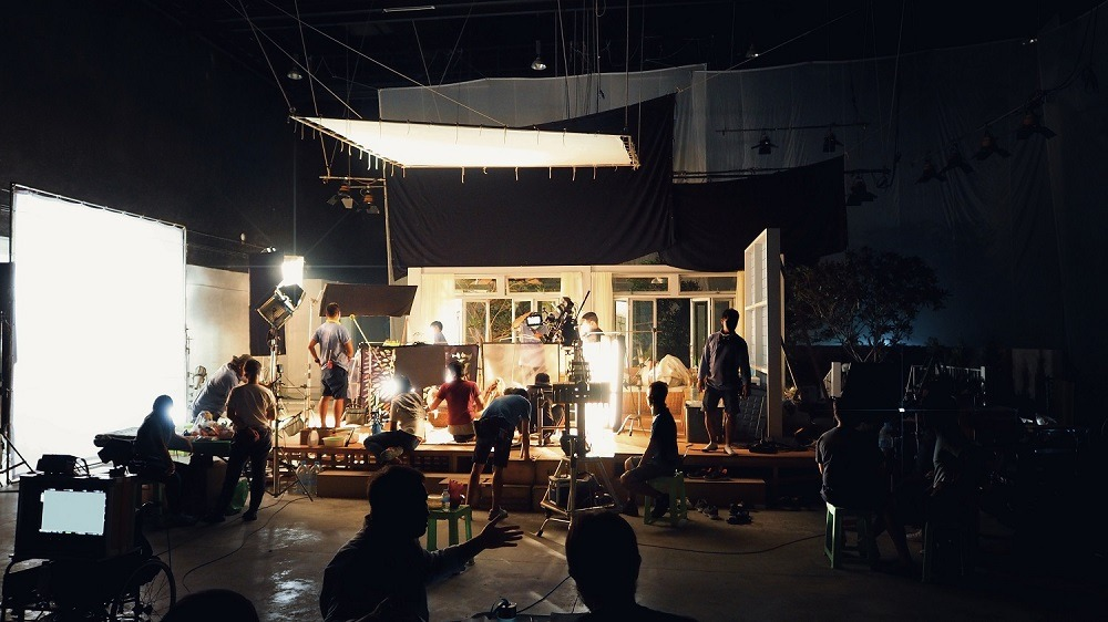 Silhouette of group of people working in a big production studio for filming.