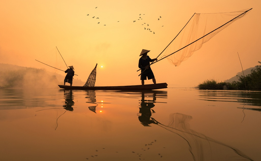 Fisherman is fishing with his son in the morning
