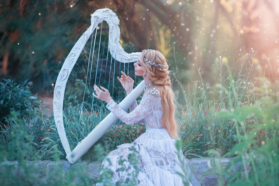 Mysterious wood nymph plays on white harp in fabulous place.