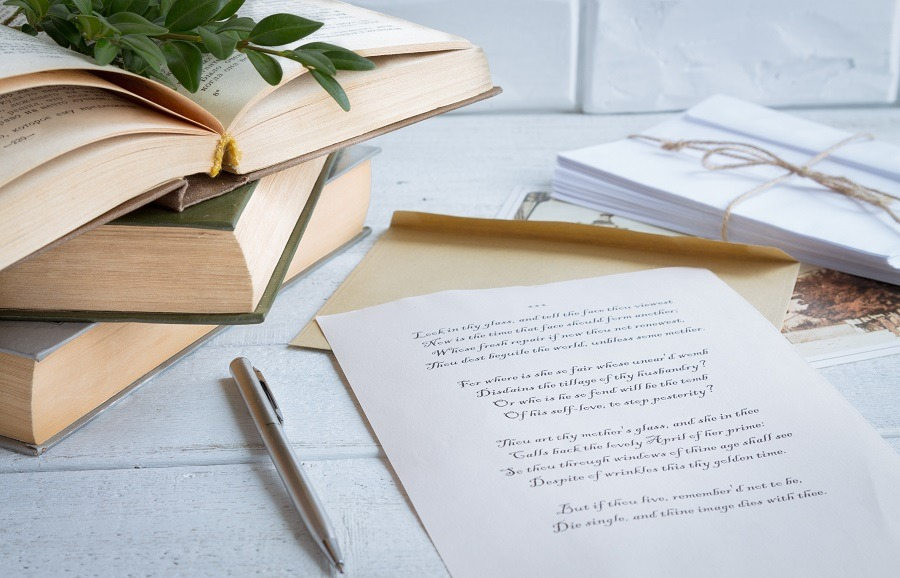 Shakespeare verse printed on beige paper with old books on a wooden background.